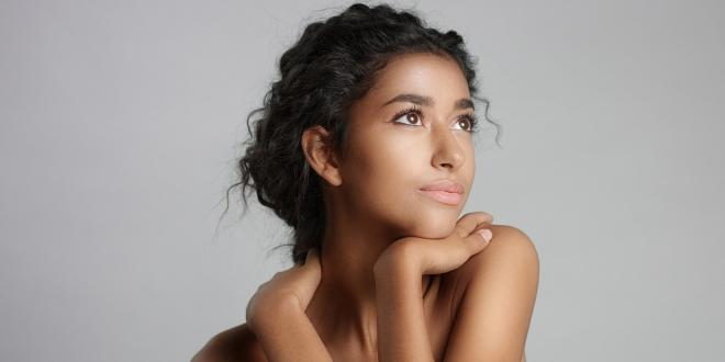 Happy serene young woman with beautiful olive skin.